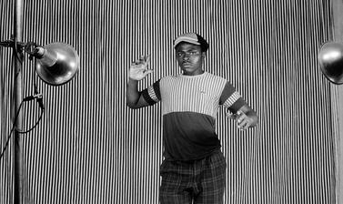 Man posing in front of a striped cloth backdrop. Photograph by Jacques Touselle. Mbouda, Cameroon. About 1980.