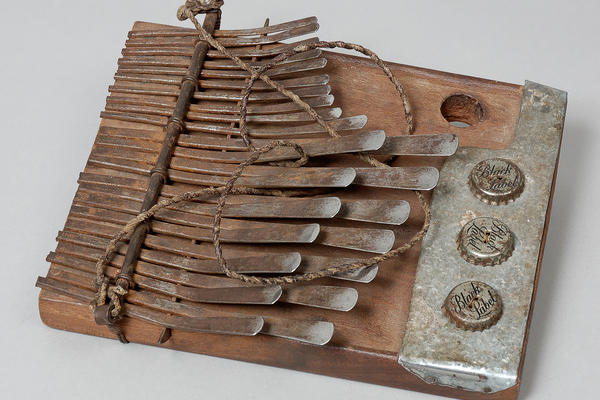 Mbira from Zimbabwe. Wooden with metal prongs & bottle caps.
