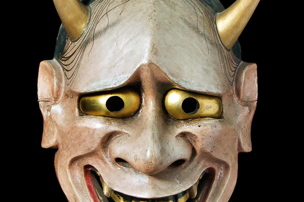 A white faced mask with two bulging eyes and a pair of horns coming out of the top of the head.
