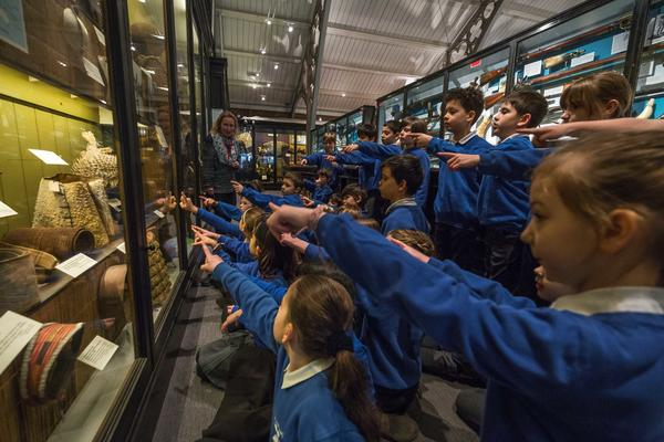 Primary school pupils sit on museum floor pointing at a puffer fish helmet which they can see in the case in front of them