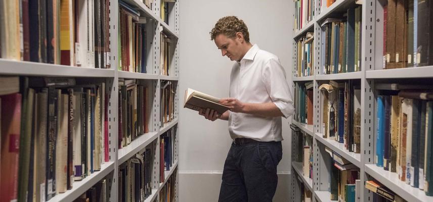 A man reading a book between two bookshelves