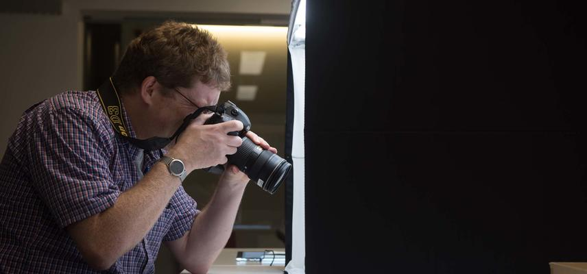 Man taking pictures using a camera and a photography light box