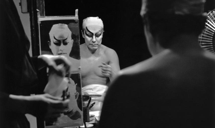 Actor Nakamura Kanzaburō XVIII preparing for his role in the kabuki play Renjishi. Here is he seen applying the thick make-up known as kumadori ('shadow painting'), one of kabuki theatre's most distinctive features. The photograph on Kanzaburō's mirror sh