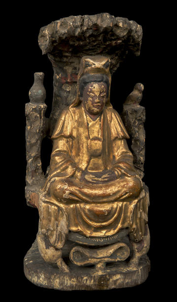 A gold wooden figure seated in a grand chair under a bush.