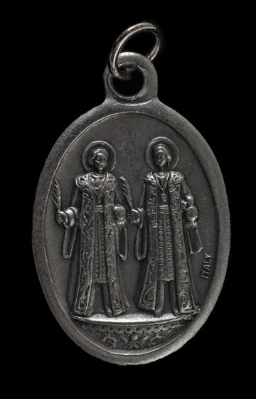 Oval metal pendant with two figures dressed in robes, each with a halo around their head.