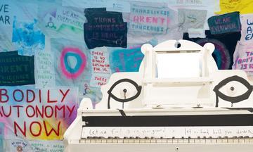 Beyond the Binary banner with activist slogans behind white harmonium