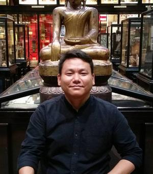 Thupten Kelsang in the Pitt Rivers Museum mimicking the pose of a buddha statue